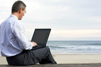 Man using laptop to access digital files on beach.